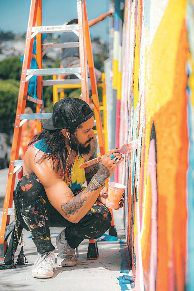 Brazilian-born artist Guilherme Lemes works on a mural.
